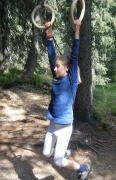 girl holding onto handles, swinging